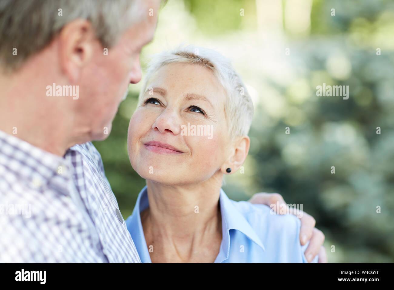 Retrato de amorosa pareja abrazada senior y mirando a uno y otro enfoque sobre la elegante mujer sonriente al marido, espacio de copia Foto de stock