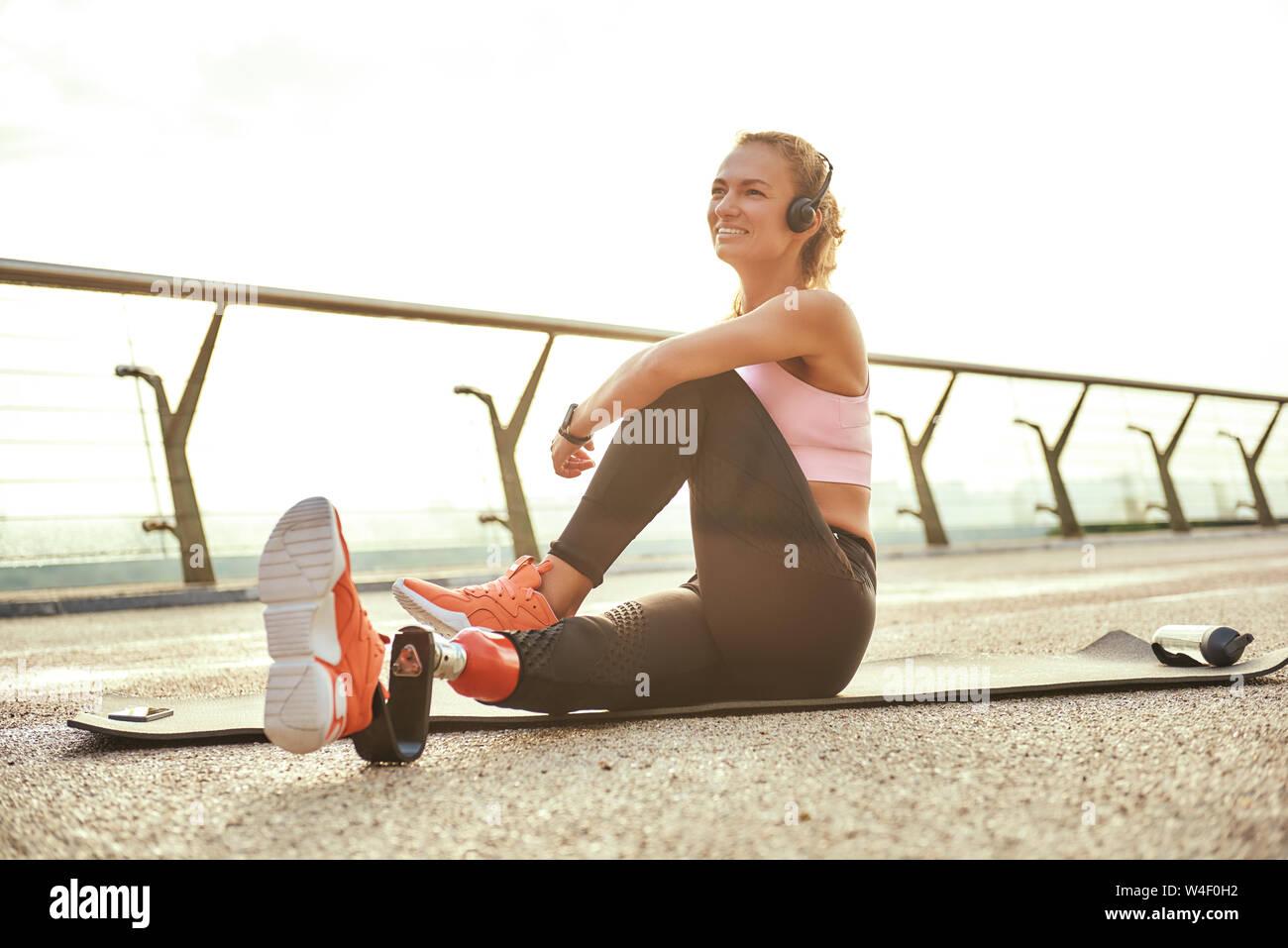 Feliz por la mañana. Atletas discapacitados positiva mujer con pierna prostética en auriculares haciendo ejercicios de yoga y sonriendo mientras estaba sentado en el puente. Deshabilitado el deporte concepto. La motivación. Estilo de vida saludable Foto de stock