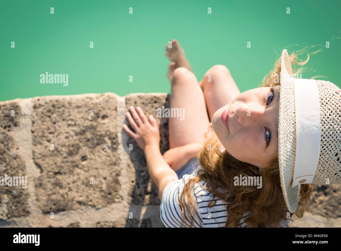 Vista aérea de la niña con sombrero de paja, sentado en la piscina, en la Toscana, Italia Foto de stock