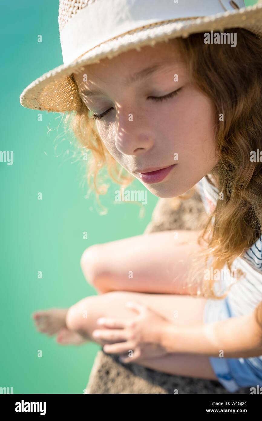 Chica sentada en la piscina, soñando, Toscana, Italia Foto de stock