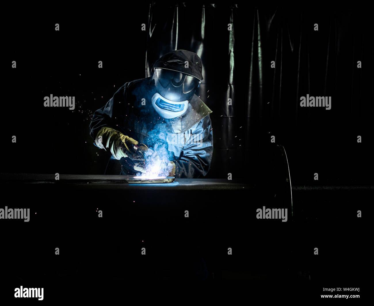 Trabajador industrial en ropa protectora de metal de soldadura con soplete Foto de stock