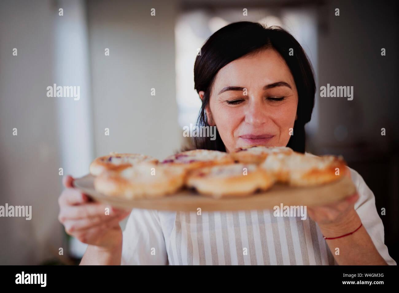 Mujer madura que sirve tartas caseras ona bandeja de madera Foto de stock