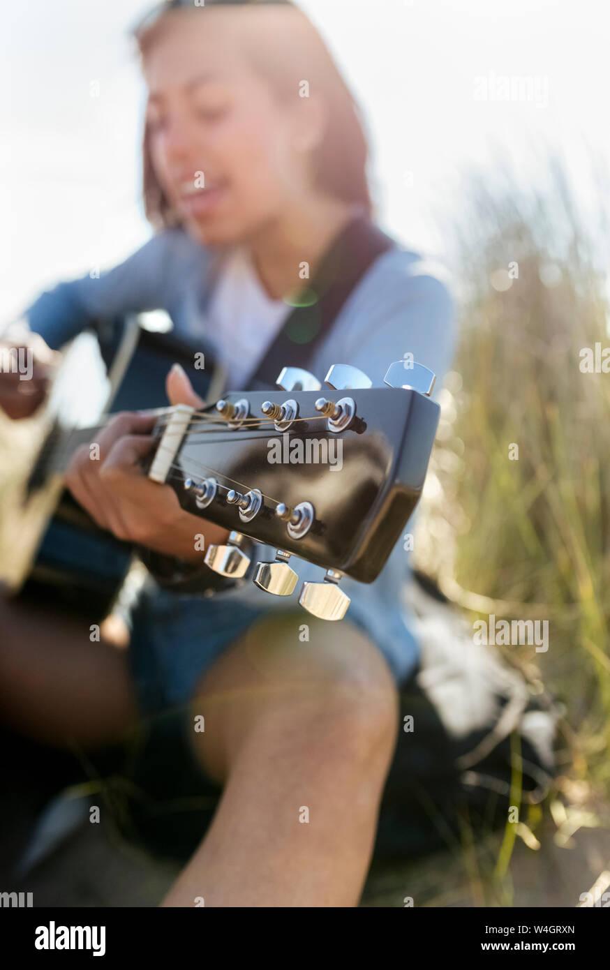 Close-up de joven cantando y tocando la guitarra en la playa Foto de stock