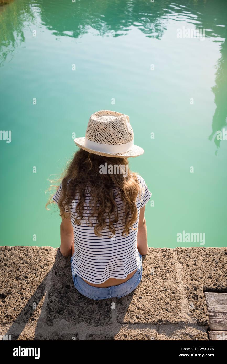 Vista posterior de una muchacha sentada en la piscina, en la Toscana, Italia Foto de stock