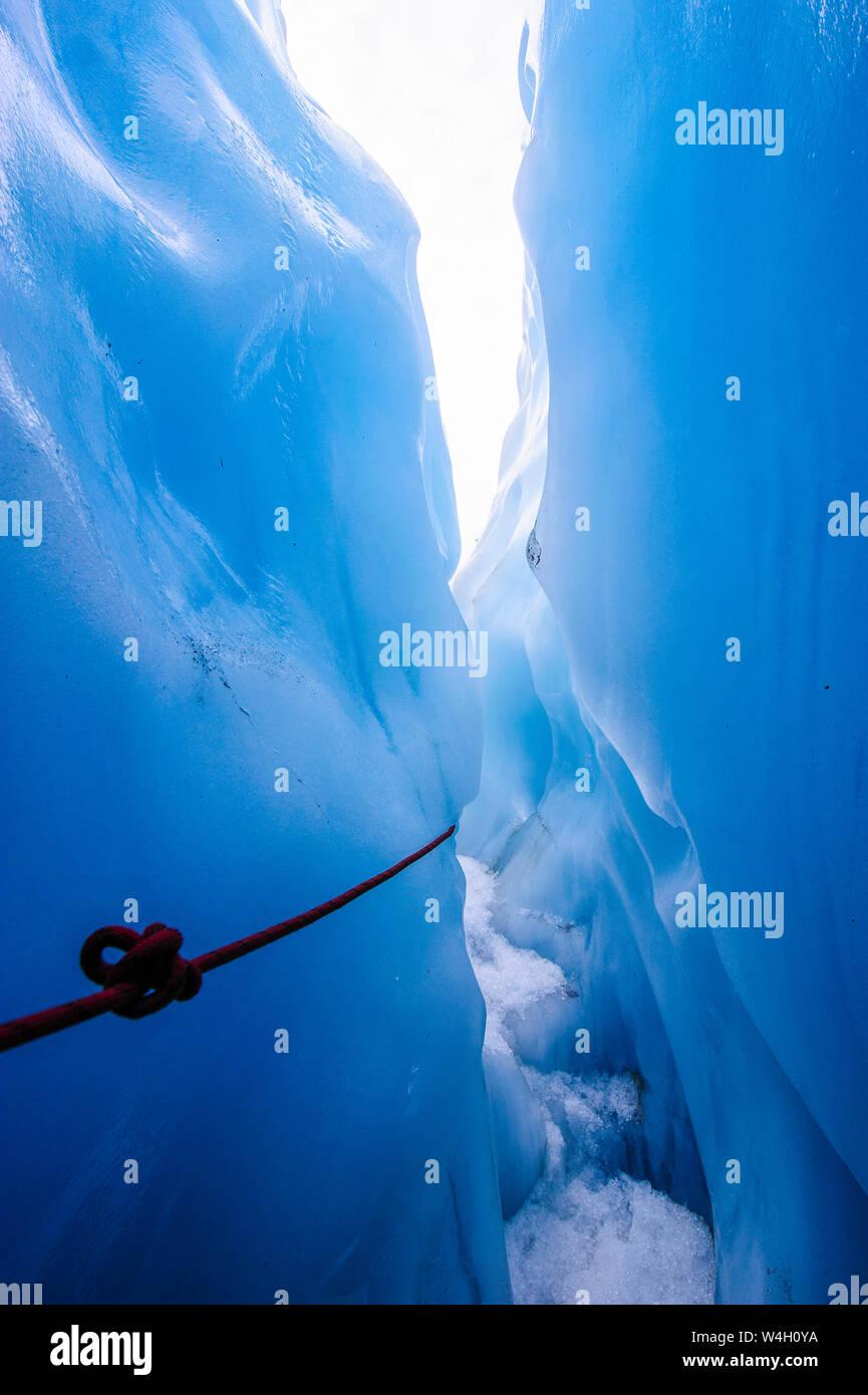 La cuerda en una cueva de hielo en el glaciar Fox, Isla del Sur, Nueva Zelanda Foto de stock