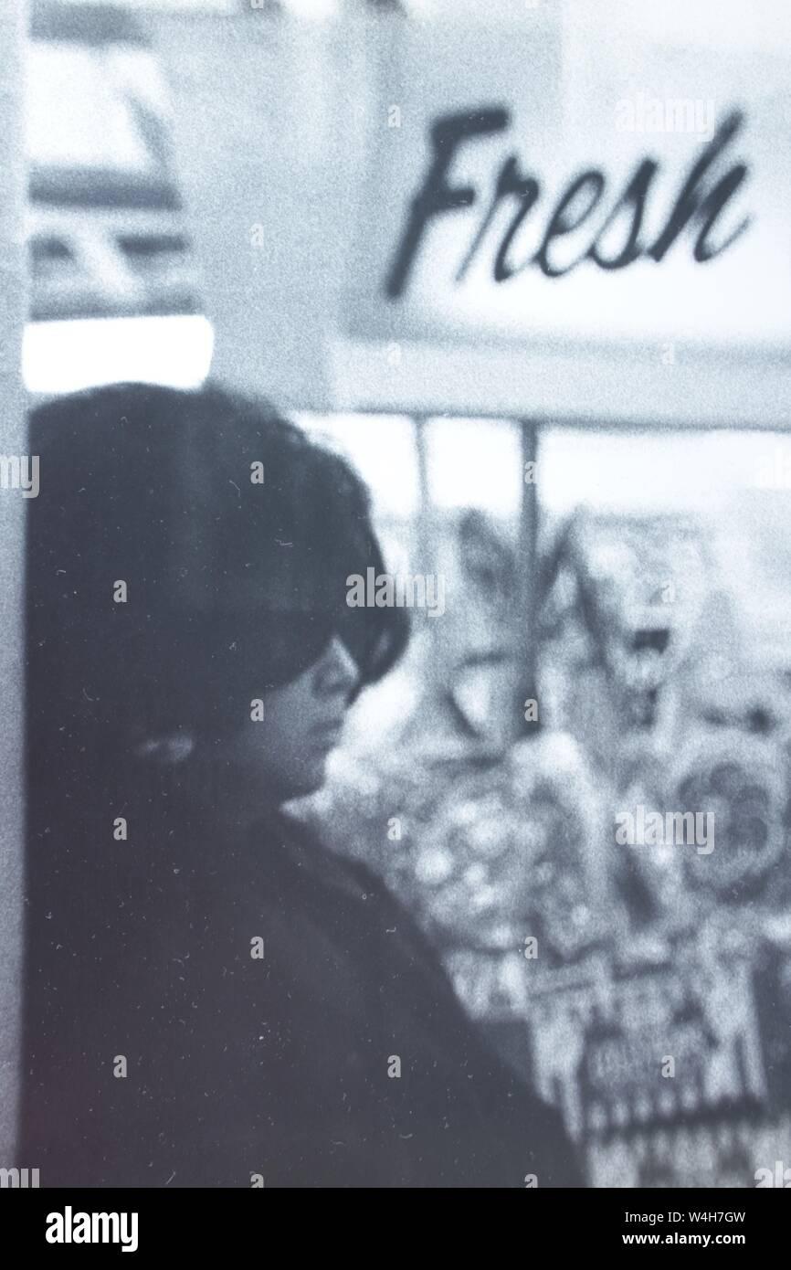 """Fino arte fotografía en blanco y negro a partir de la década de 1970 de una elegante mujer de incógnito con un par de gafas de sol oscuras pesado pasando un signo """"fresco"""". Foto de stock"""