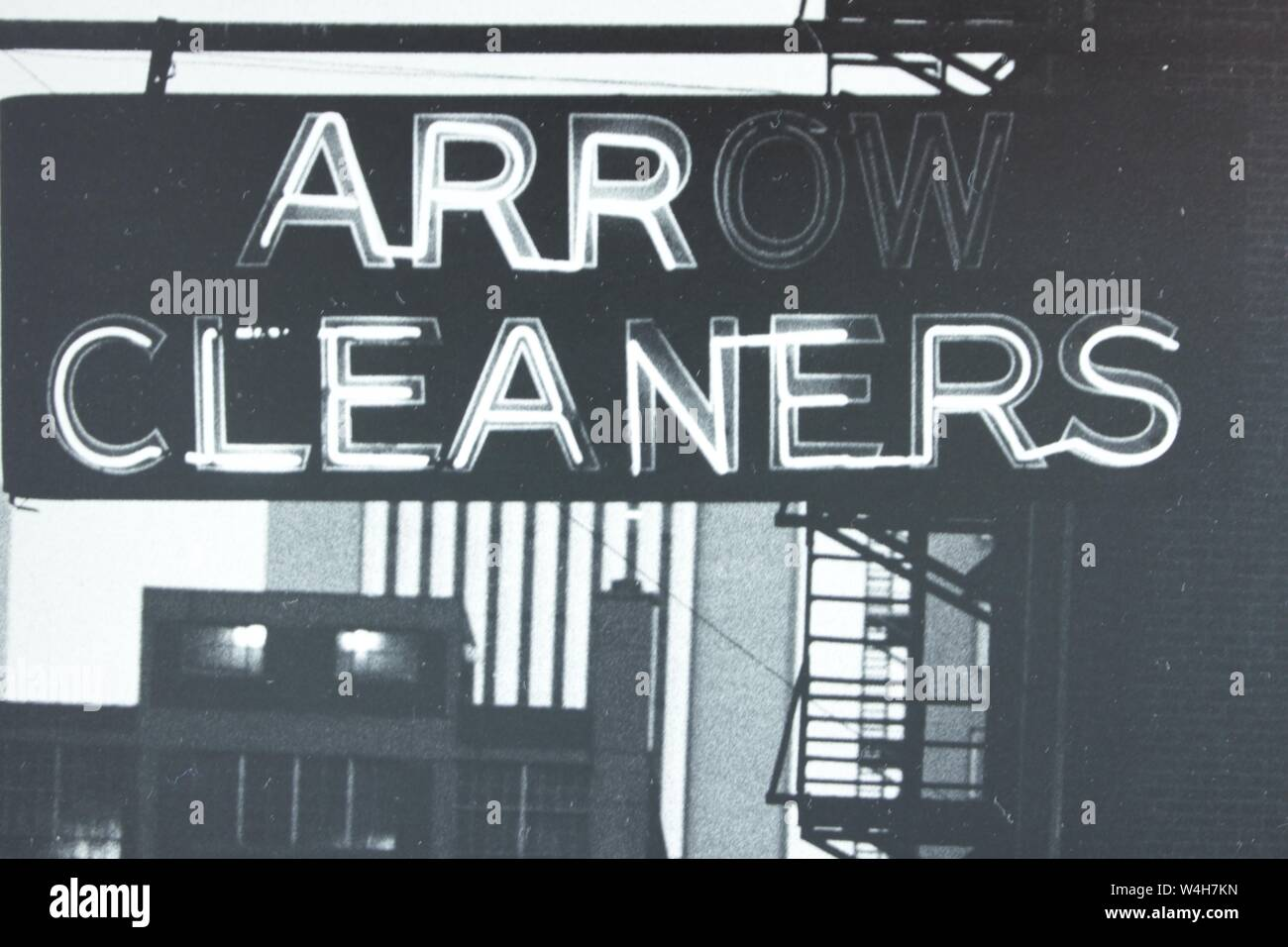 Fino arte fotografía en blanco y negro a partir de la década de 1970 de un cartel de neón de limpiadores de flecha. Foto de stock