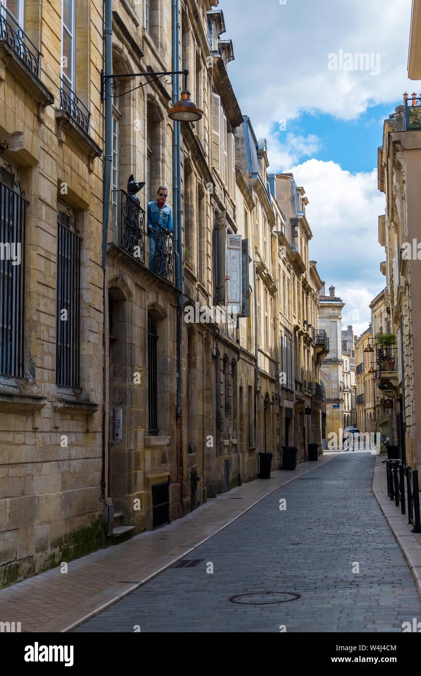 Burdeos, Francia - 5 de mayo de 2019: maniquí de un gato negro y un hombre en el balcón de un edificio residencial en el centro histórico de la ciudad de Bordeaux, Francia Foto de stock