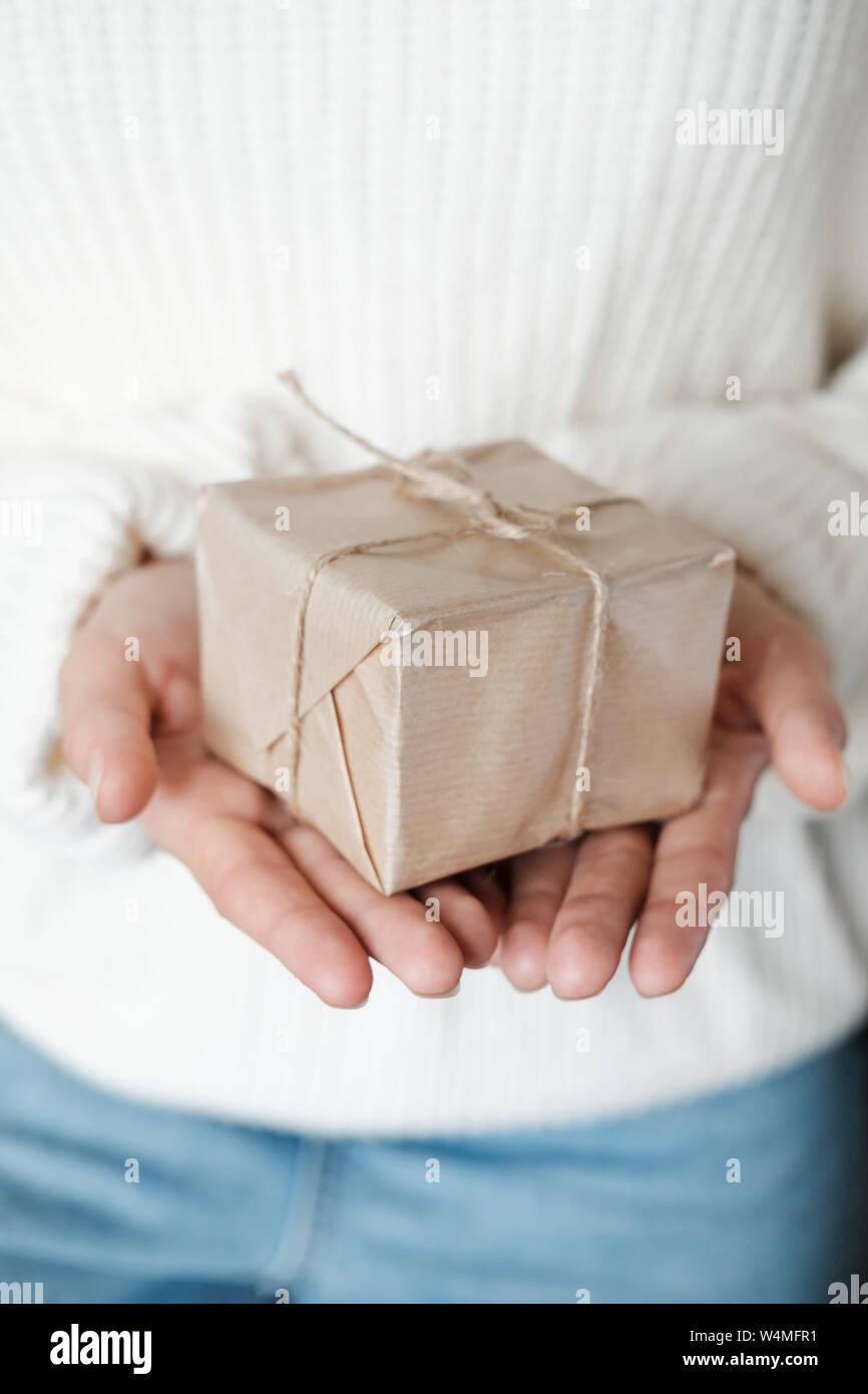 Mujer de Blanco suéter tejidos dando envuelto de regalo. Cerrar manos femeninas celebración Caja Navidad presente. Navidad, Año Nuevo, compras, preparación o Foto de stock