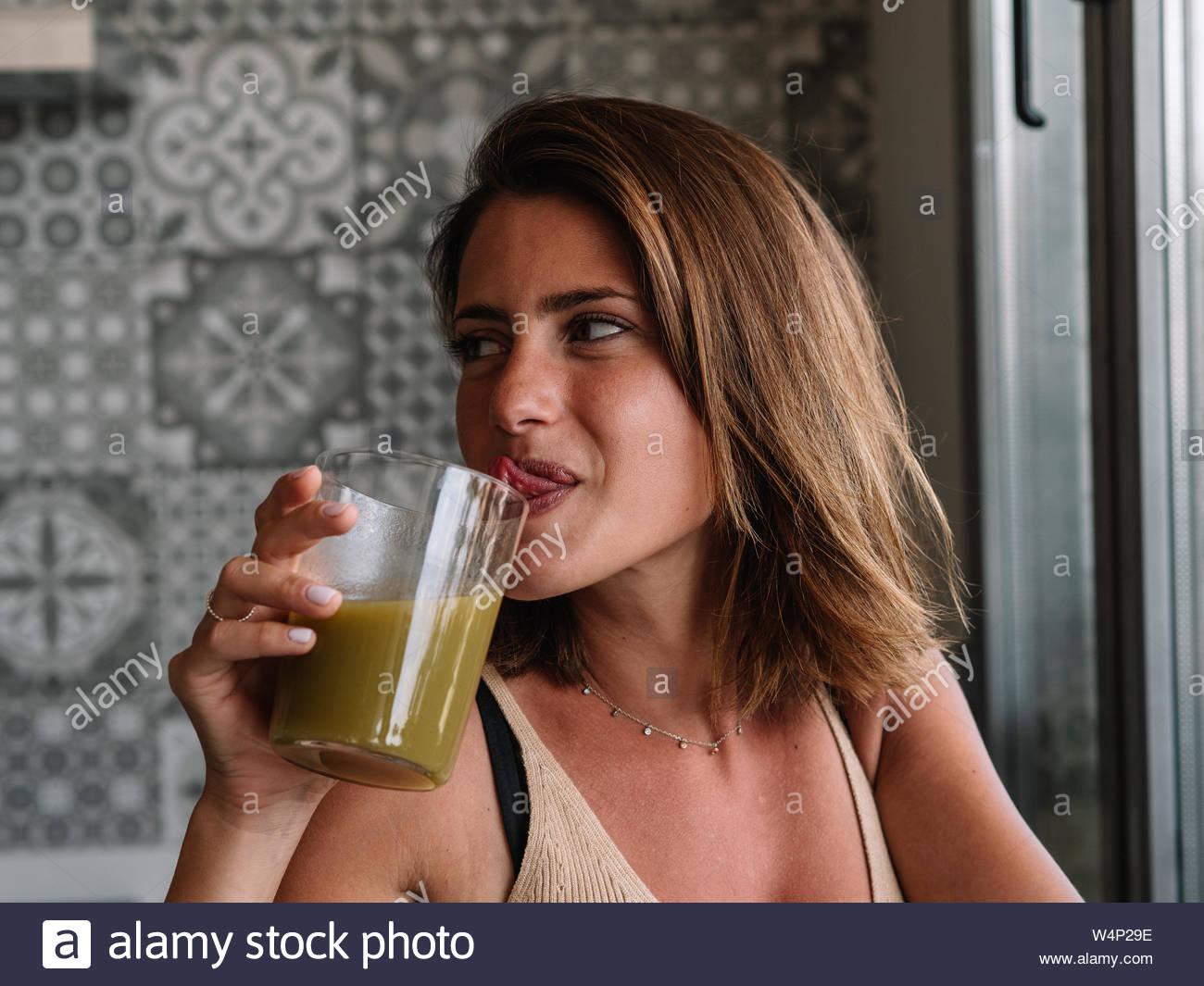 Chica caucásica es tener un jugo de vegetales de color verde en la parte delantera de su gran ventana de la cocina Foto de stock