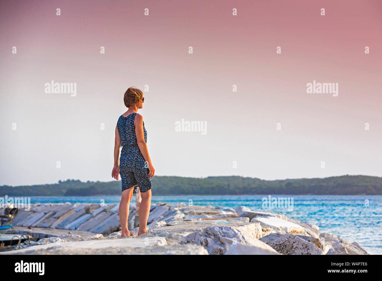 Croacia, Istria, par disfrutar del atardecer en el muelle Foto de stock