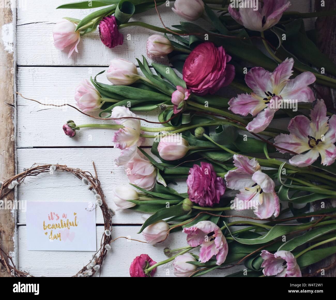 Tulipanes rosados y ranúnculos con una tarjeta diciendo que es un hermoso día Foto de stock