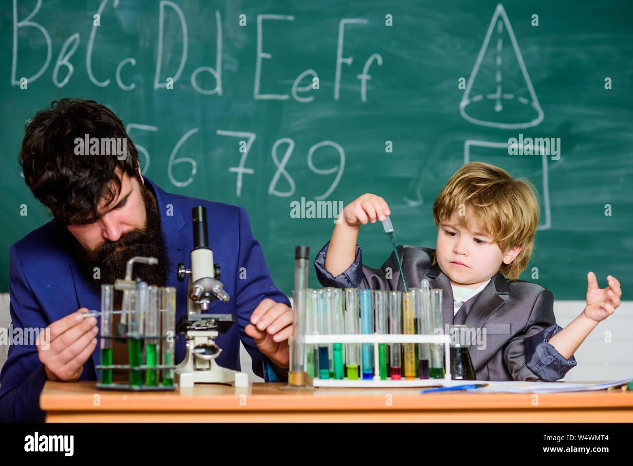 El conocimiento es deliciosa. La escuela kid científico que estudia la ciencia. maestro Hombre con Little Boy. Al regresar a la escuela. El padre y el hijo en la escuela. Chiquillo aprender química en la escuela laboratorio. Foto de stock