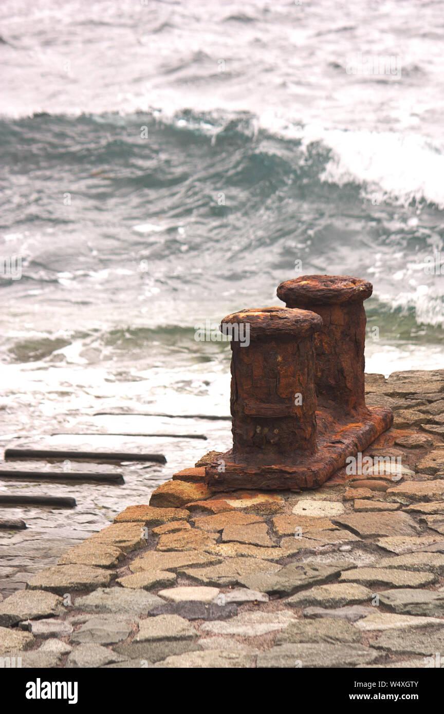 Visión vertical de un pequeño puerto con el viejo y oxidado noray con las olas del mar en el fondo Foto de stock