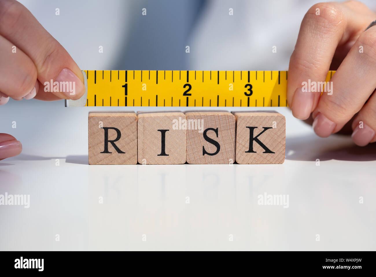 Close-up de una empresaria de la mano de medir el riesgo de bloques con la cinta de medición AMARILLA Foto de stock