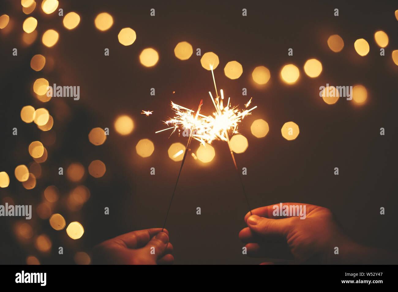 Feliz Año Nuevo. Brillantes estrellitas en manos sobre fondo de oro, un par de luces del árbol de Navidad La celebración festiva en la oscuridad de la habitación. Espacio para el texto. Fir Foto de stock