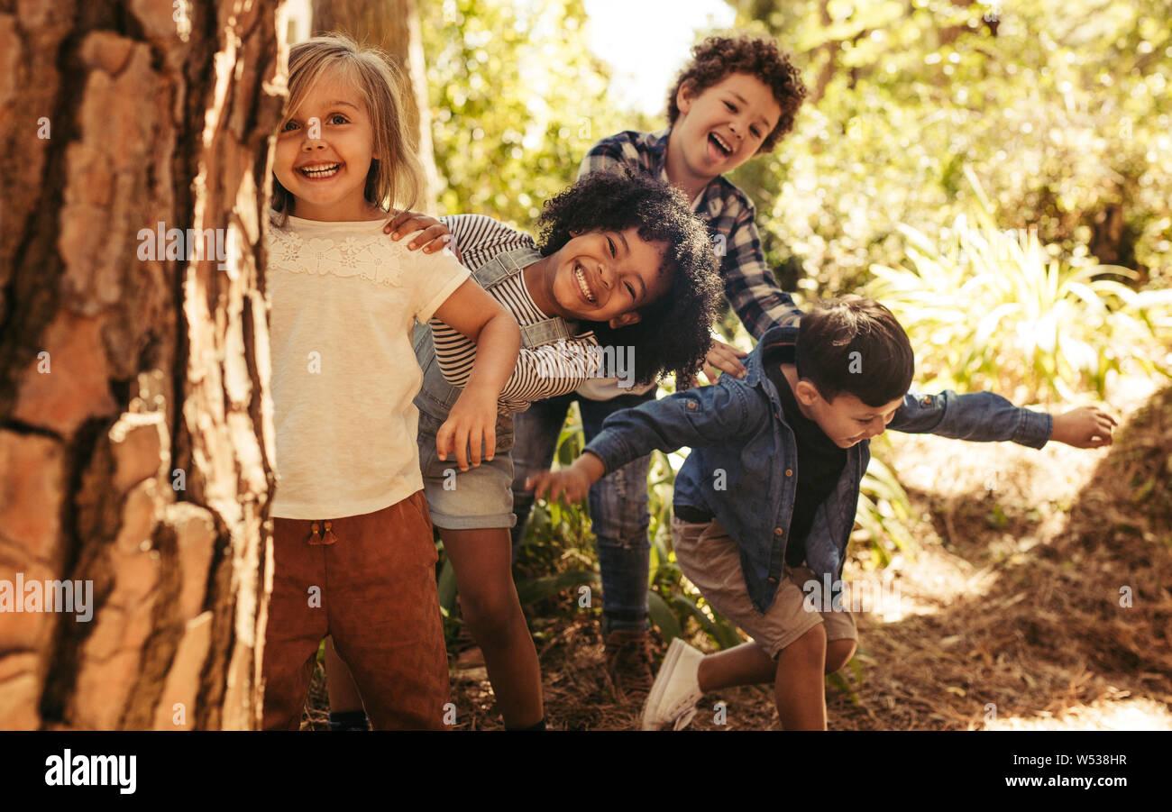Lindo niños sonrientes que sobresale desde detrás del árbol en el parque. Grupo de niños disfrutan jugando al escondite en un bosque. Foto de stock