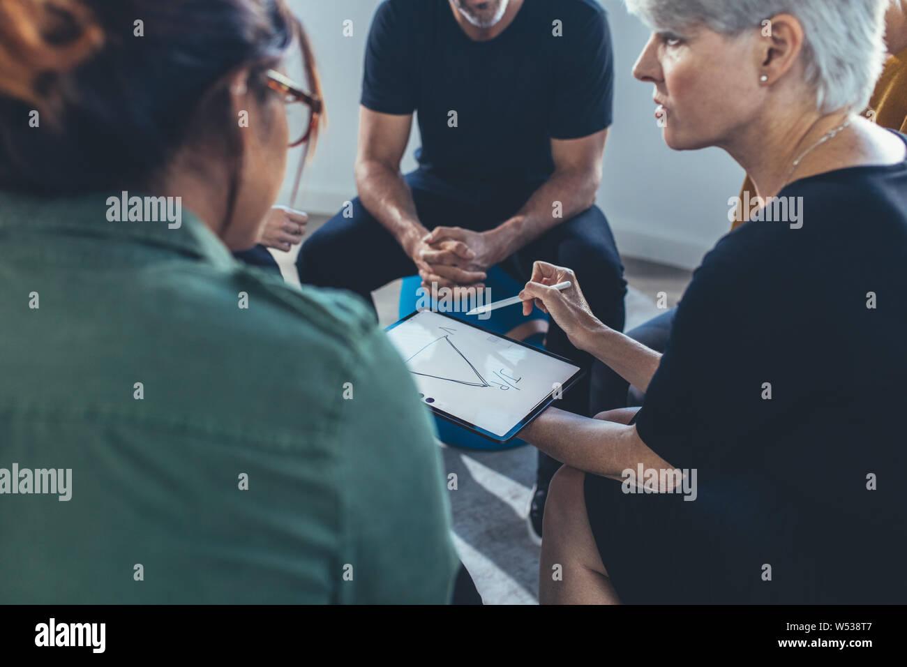 Mujer de negocios maduros para explicar la estrategia para el equipo en una reunión. Grupo multiétnico de gente sentada junto con una reunión. Foto de stock