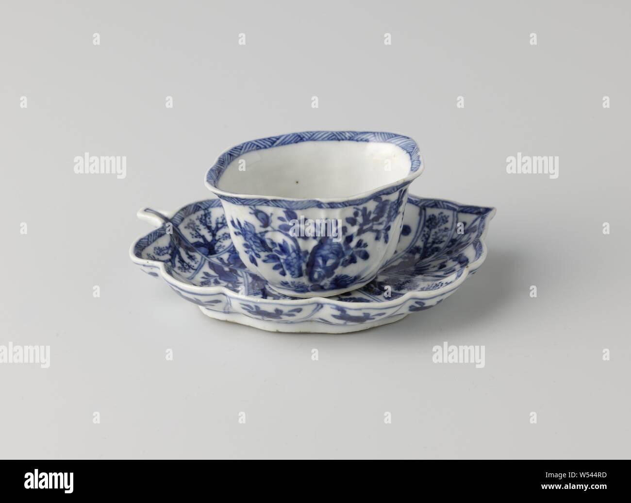 """Taza con platillo en forma de una hoja, taza y plato de porcelana, el platillo en la forma de una hoja, pintado de azul underglaze. La cabeza modelada con venas en el exterior y pintados con una rama de flores flores cuatro veces, una rama de flores en la parte inferior, el interior y el exterior del borde con una banda decorativa con la eclosión. El plato está dividido con una caja decoración por los """"ins"""" de la hoja, llena de diversas plantas en floración en una roca. Marcados en la parte inferior del plato con un lotus. Azul Blanco., anónimos, China, c. 1750 - c. 1774, la dinastía Qing (1644-1912) / Periodo Qianlong (1736-1795 Foto de stock"""
