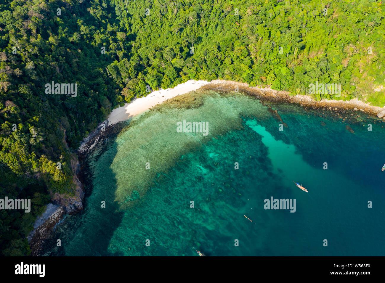 Antena drone vista de una playa pequeña en una exuberante isla tropical (Isla de la caverna) Foto de stock