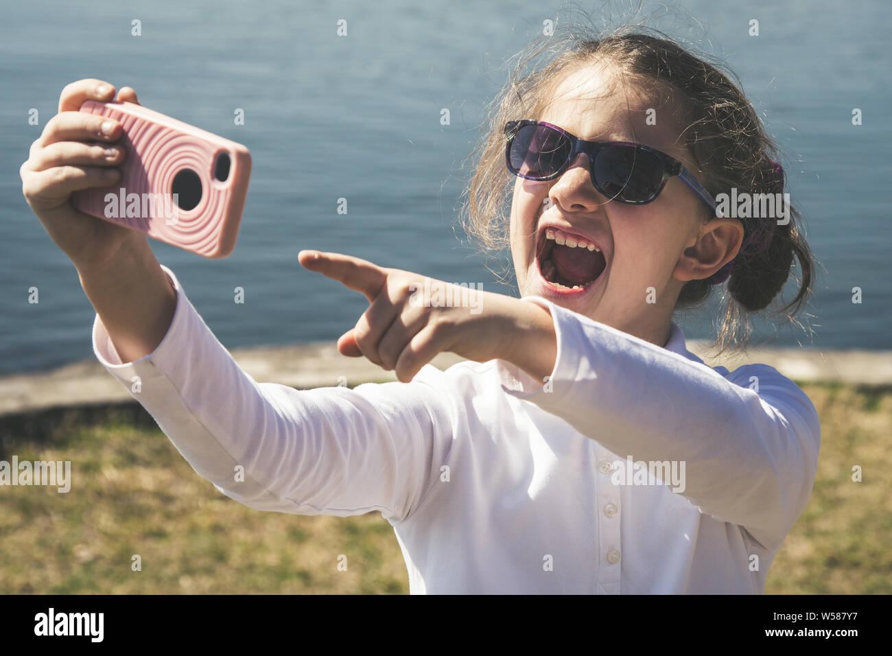 Niña hacer una videollamada con amigos tecnología inalámbrica remota ayuda a mantenerse conectado en cualquier lugar. Hermosa sonrisa kid e indica con el Foto de stock
