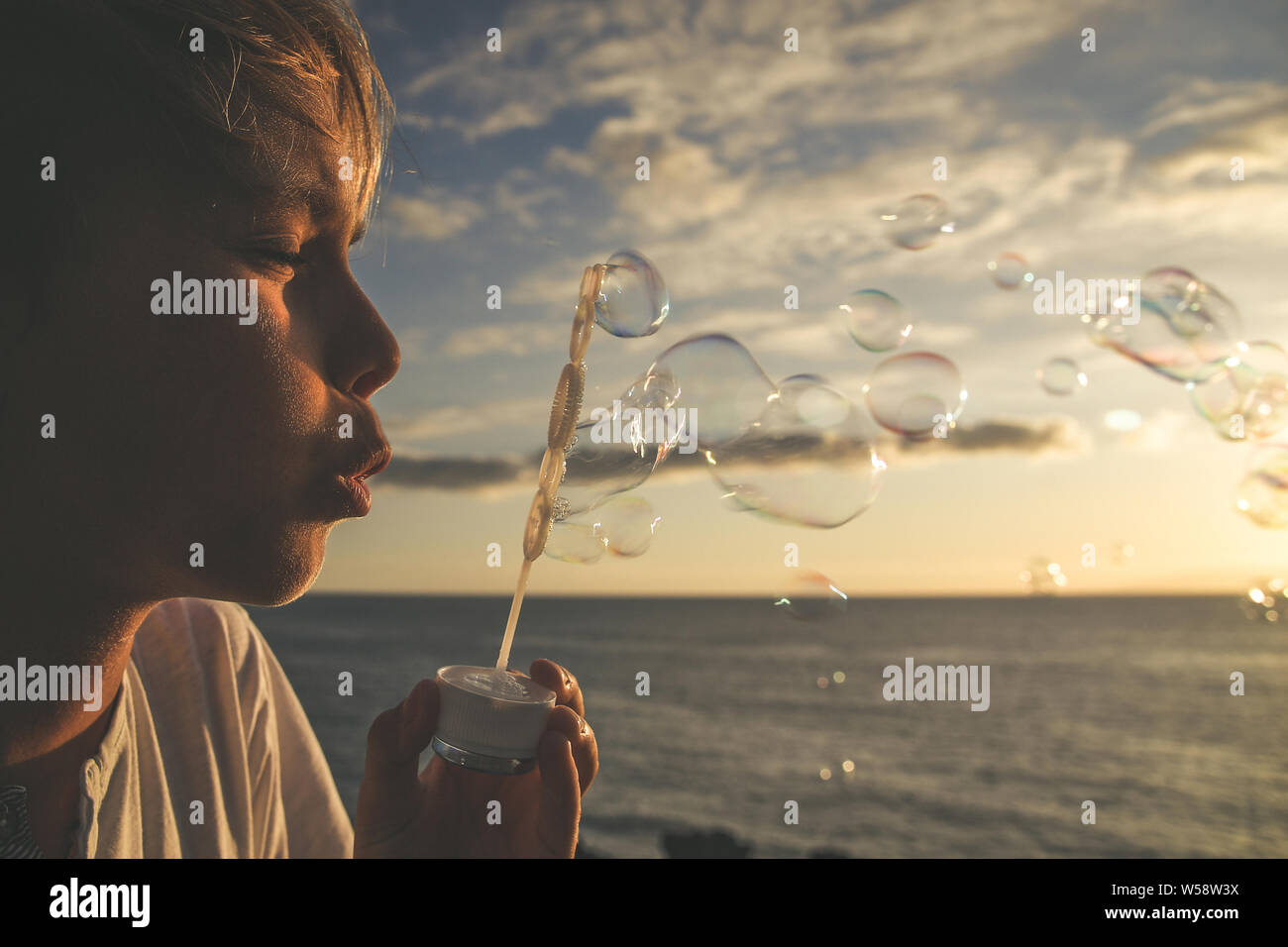 Muchacho joven rubia sopla una larga cadena de burbujas en un campo; lindo niño frente al océano persiguiendo jabón hierva, Niza kid jugar al aire libre en un hermoso Foto de stock