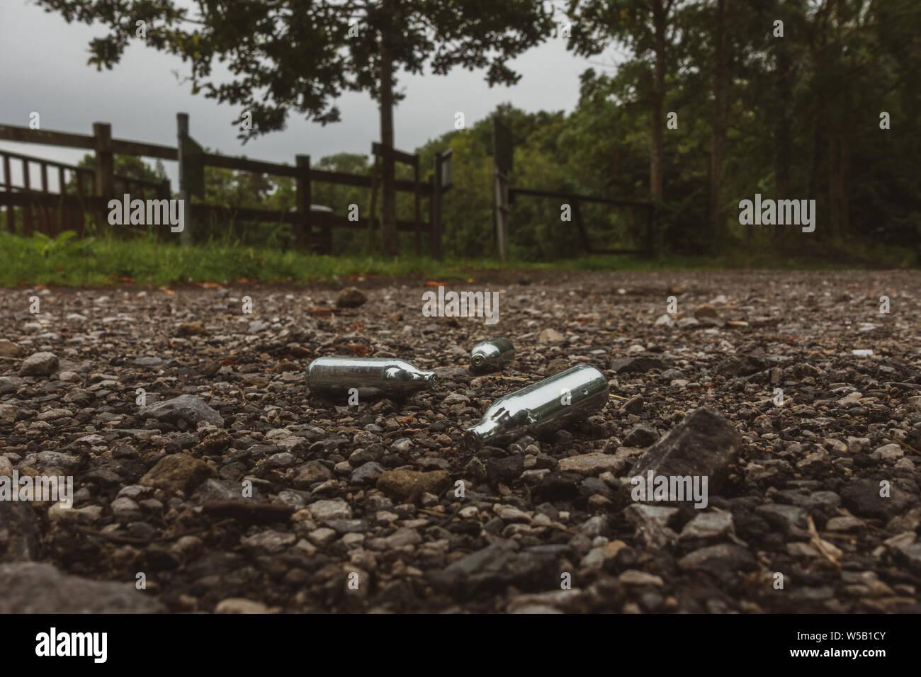 Descartan cannisters gas de óxido nitroso (gas hilarante) usada como una droga recreativa, en un parque en una zona rural. UK Foto de stock