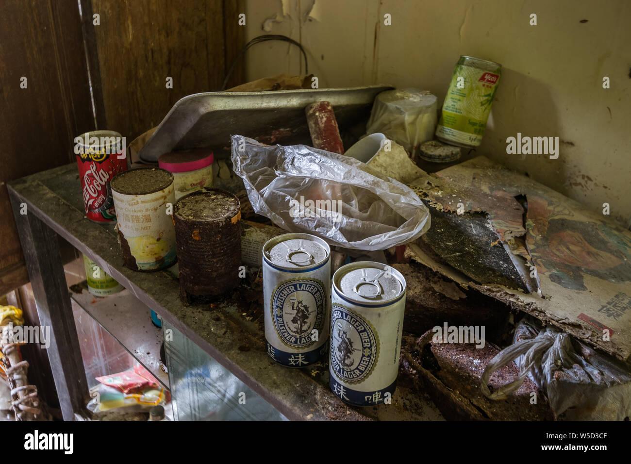 Latas oxidadas en una vitrina en la casa abandonada Foto de stock
