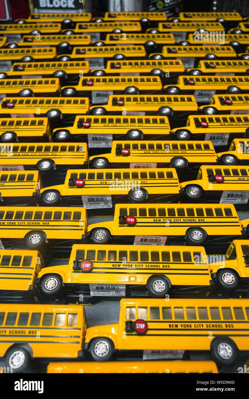 Educación en EE.UU., vista de los autobuses escolares de juguete amarillo en exhibición en una ventana de la tienda de Manhattan, Nueva York, EE.UU. Foto de stock