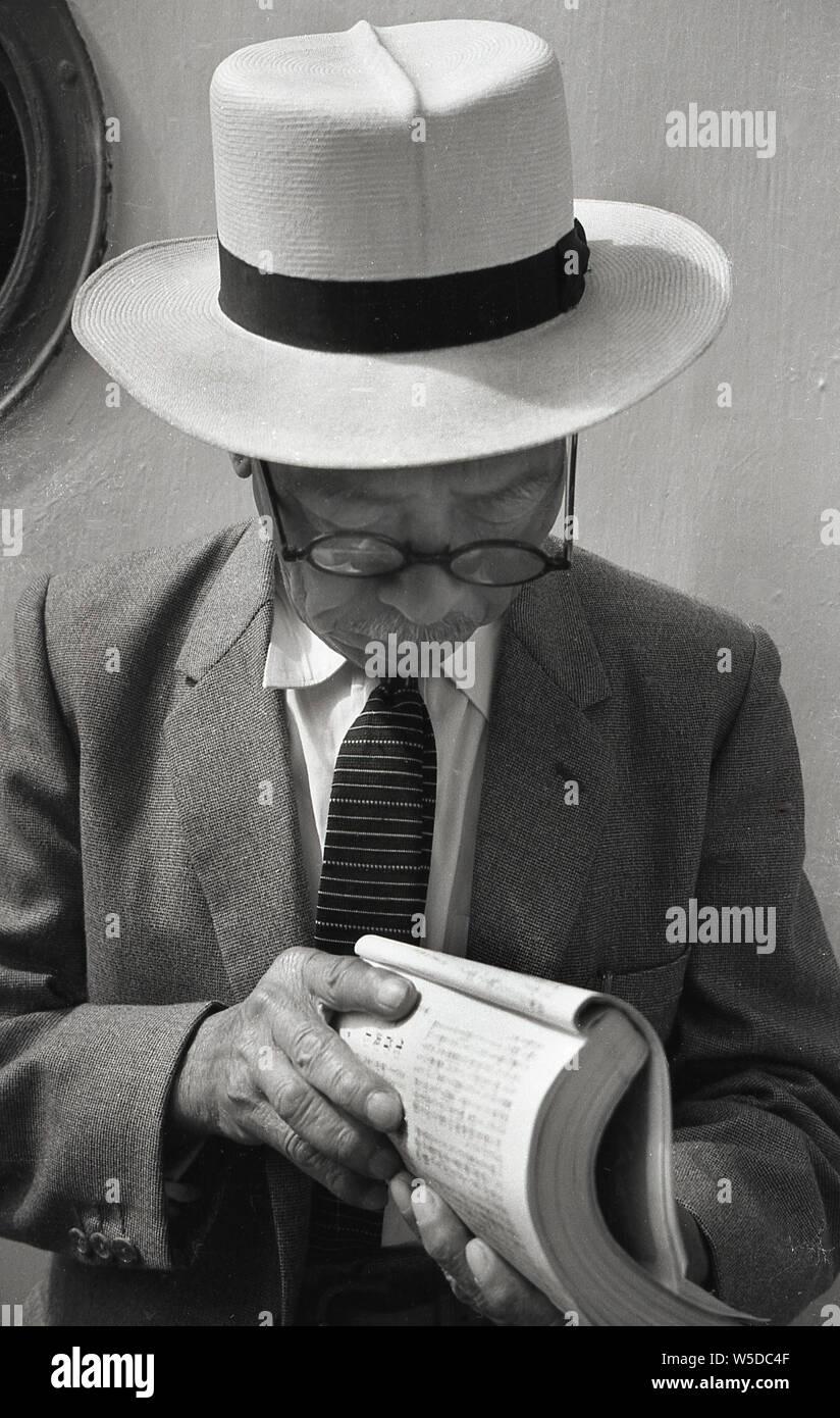[ 1950 Japón - Hombre japonés en el oeste de traje y sombrero ] - Japonés hombre que llevaba un sombrero y un traje occidental es la lectura en un barco a la isla de Awaji, Prefectura de Hyogo, 1958 (Showa 33). Foto de stock