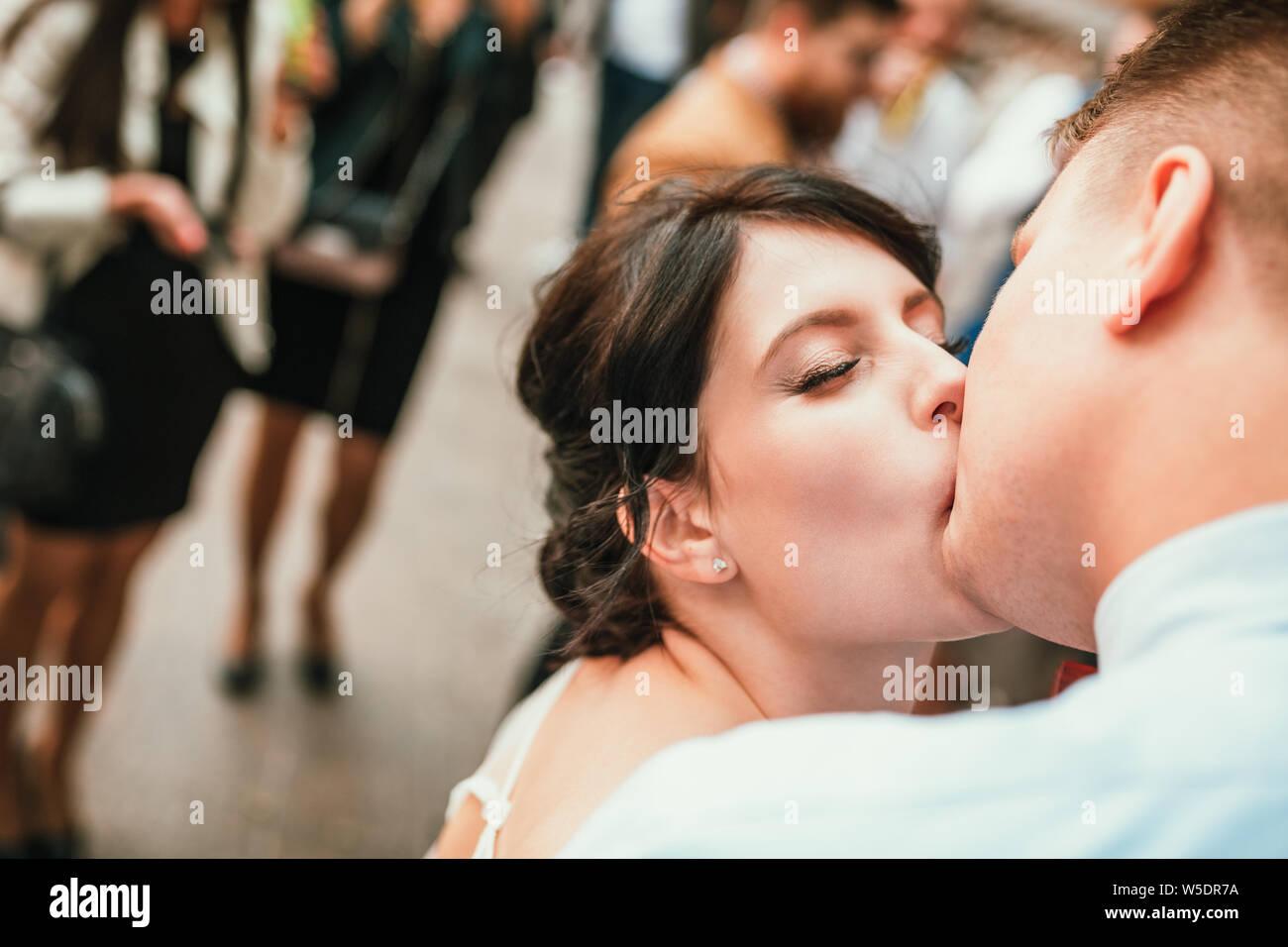 Hermosa novia y novio abrazos y besos en el día de su boda al aire libre. Concepto boda, nueva familia. Foto de stock