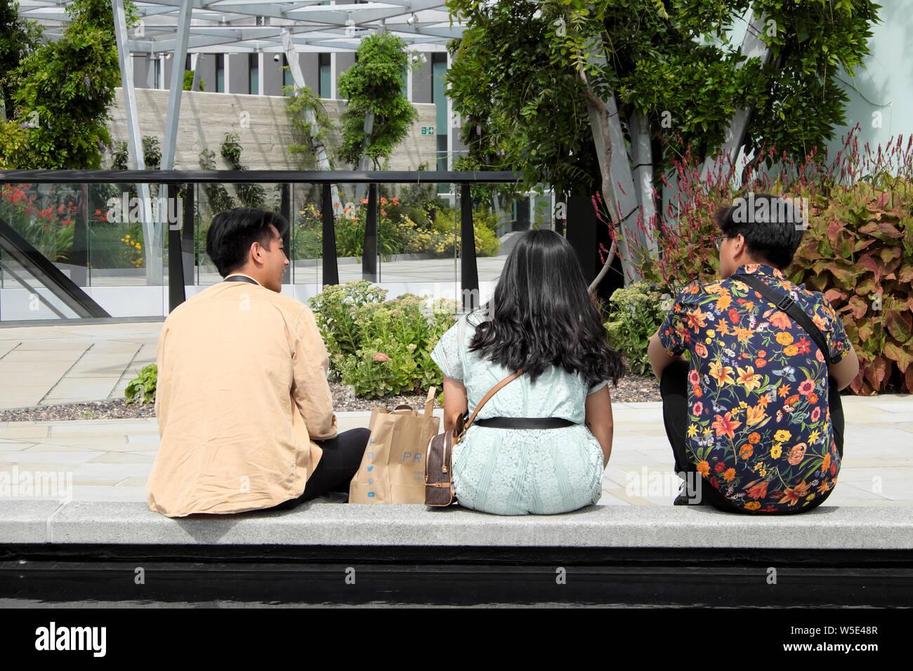Jóvenes Chinos Sentados En Un Banco En La Terraza Del Jardín