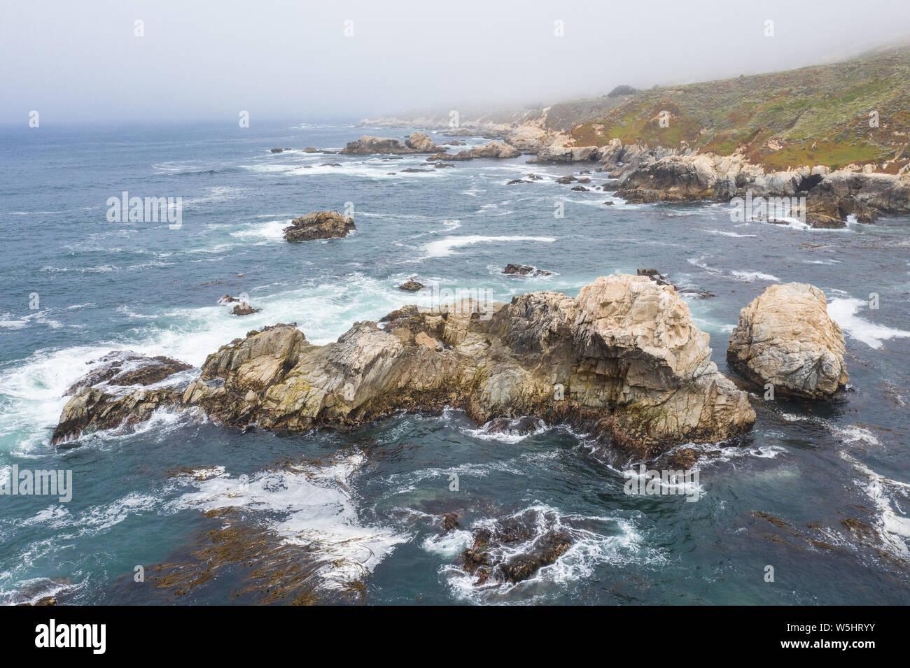 Visto desde una vista de pájaro, el Océano Pacífico baña contra el pintoresco y costa rocosa al sur de Monterrey, en el norte de California. Foto de stock