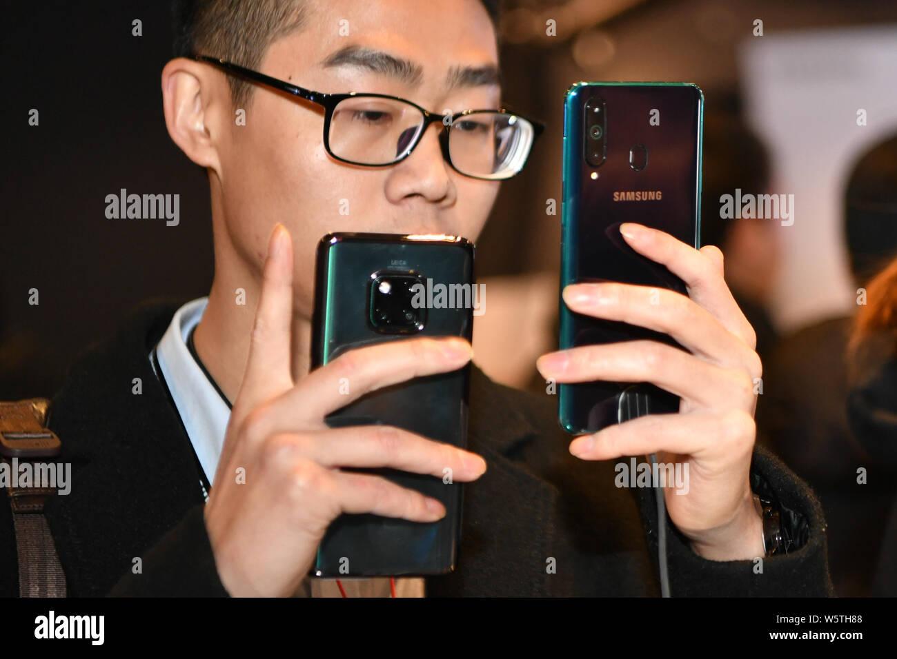 Un cliente intenta un Samsung Galaxy A8s smartphone durante el evento de lanzamiento en Beijing, China, 10 de diciembre de 2018. Samsung anuncia su primer Infini Foto de stock