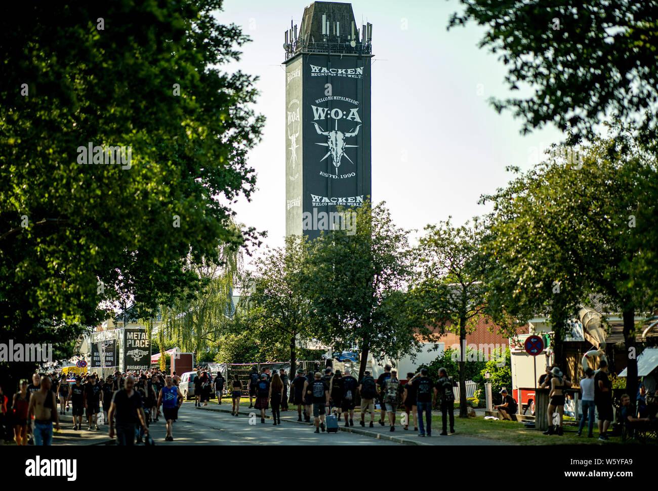 Wacken, Alemania. El 30 de julio, 2019. Los visitantes de la Wacken-Festival caminar a lo largo de la calle principal de la villa. El viaje al Festival Meatö más grande en el mundo, según los organizadores está en pleno apogeo. Crédito: Axel Heimken/dpa/Alamy Live News Foto de stock