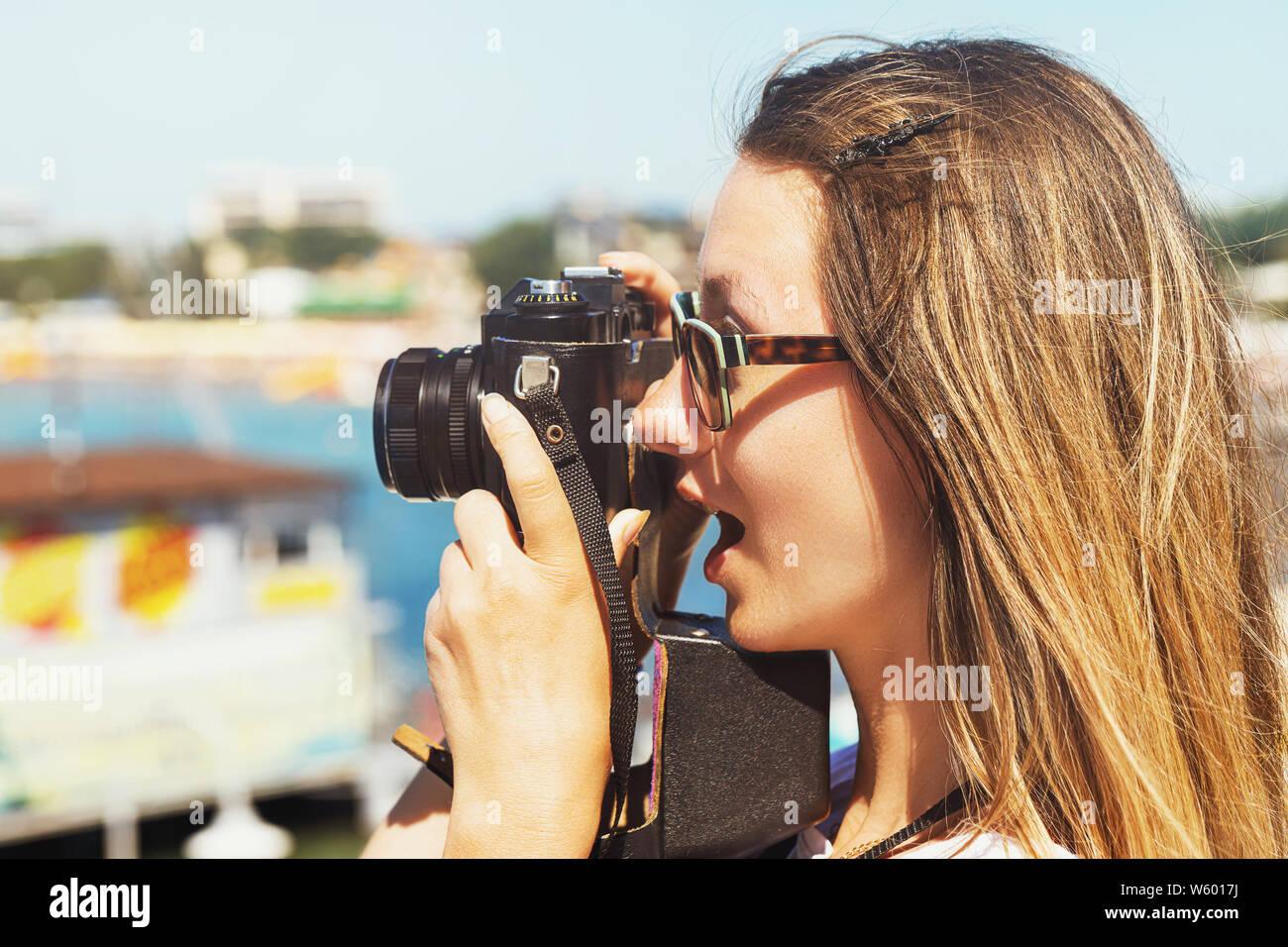 Sorprendido chica toma fotografías de paisajes, paseando a lo largo del terraplén junto al mar, cerca de la Foto de stock