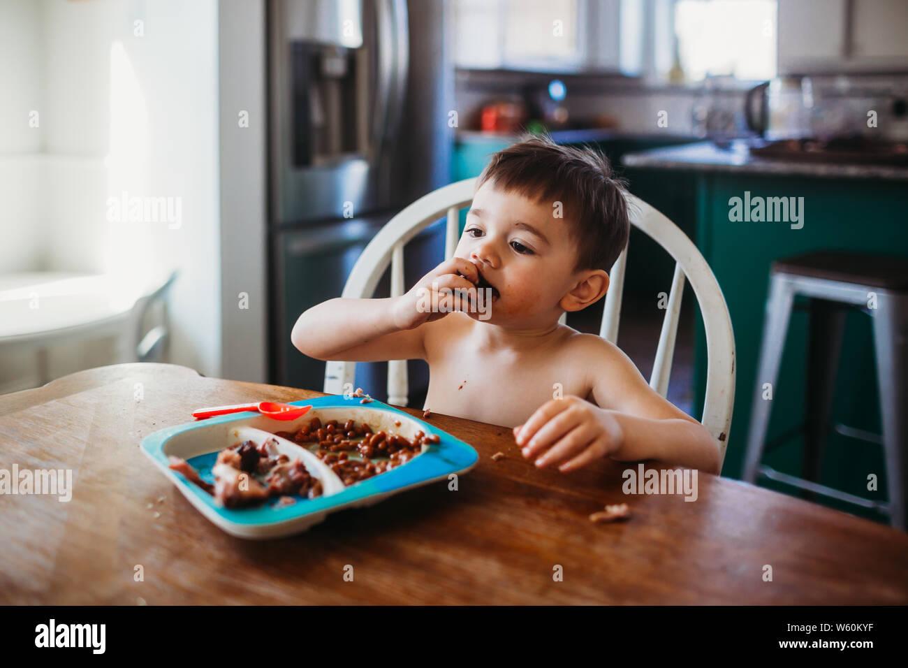 Joven comiendo costillas mientras está sentado en la mesa de comedor Foto de stock