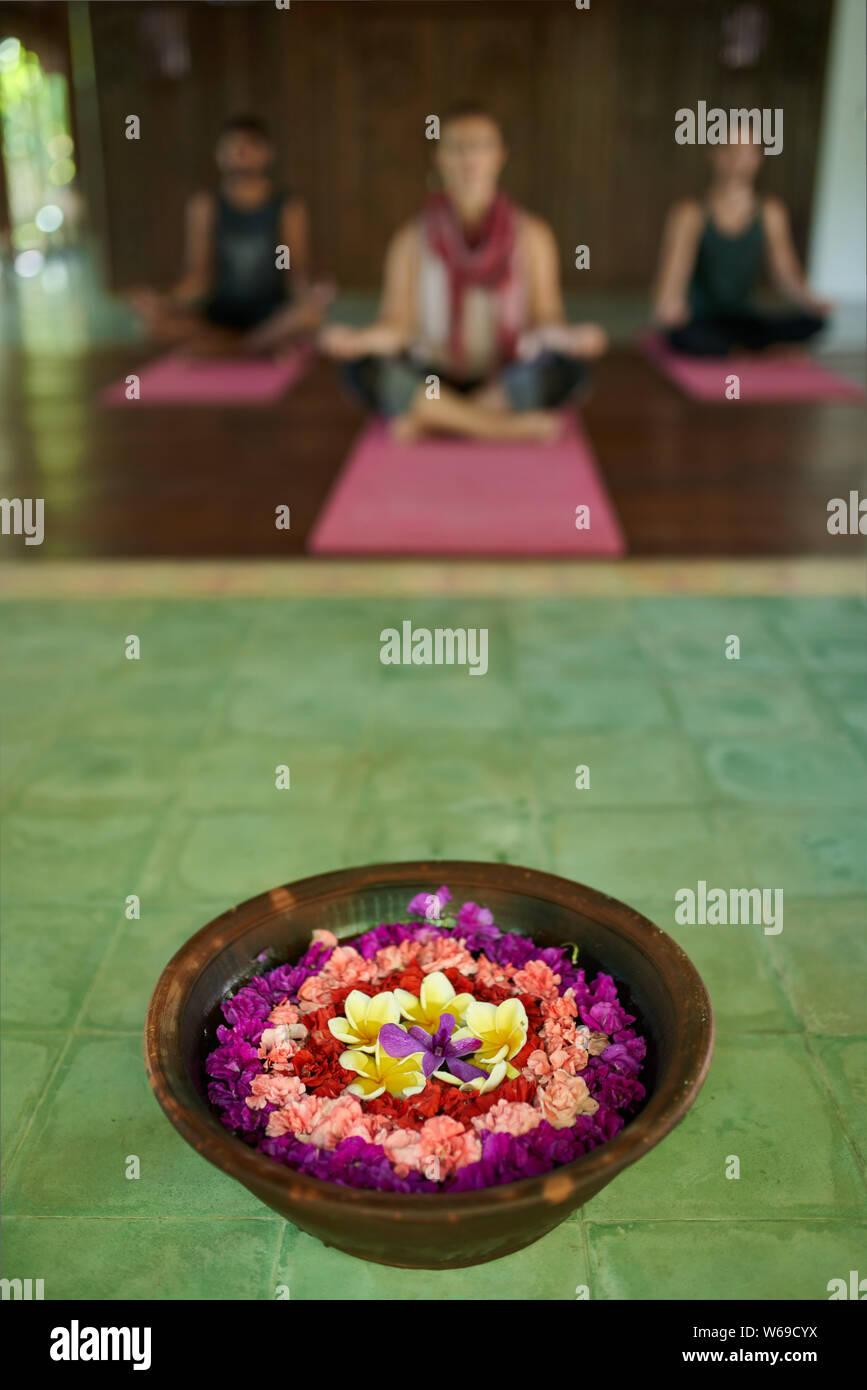 Cierre de la ofrenda de flores a la oración en el templo tradicional indonesio de Bali con tres diferentes personas meditando en segundo plano. Foto de stock