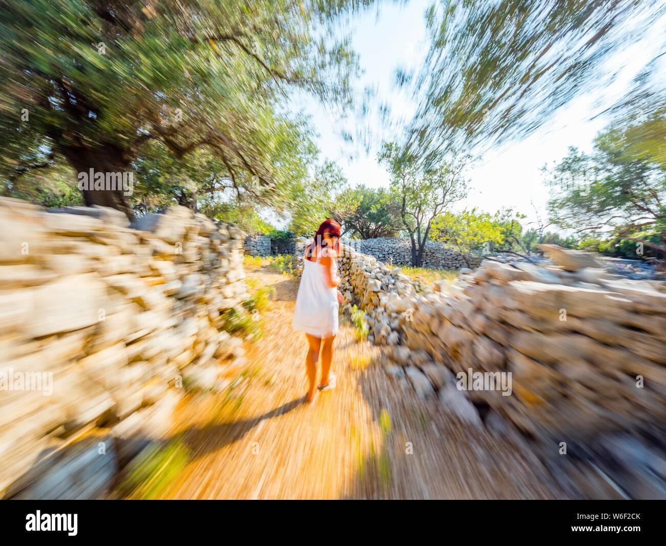 Mujer vistiendo White sundress está huyendo de la cámara mirando hacia atrás sobre el hombro seguido acechado MR Foto de stock