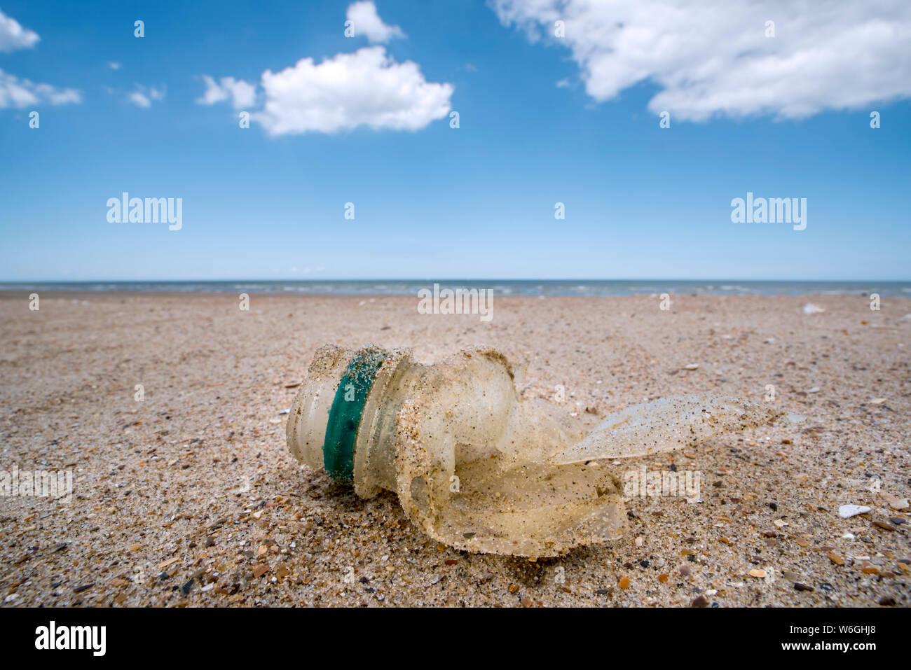 Desglosado en parte vieja botella de plástico, desechos no biodegradables arrojado por el mar en la playa de arena en la costa del Mar del Norte Foto de stock