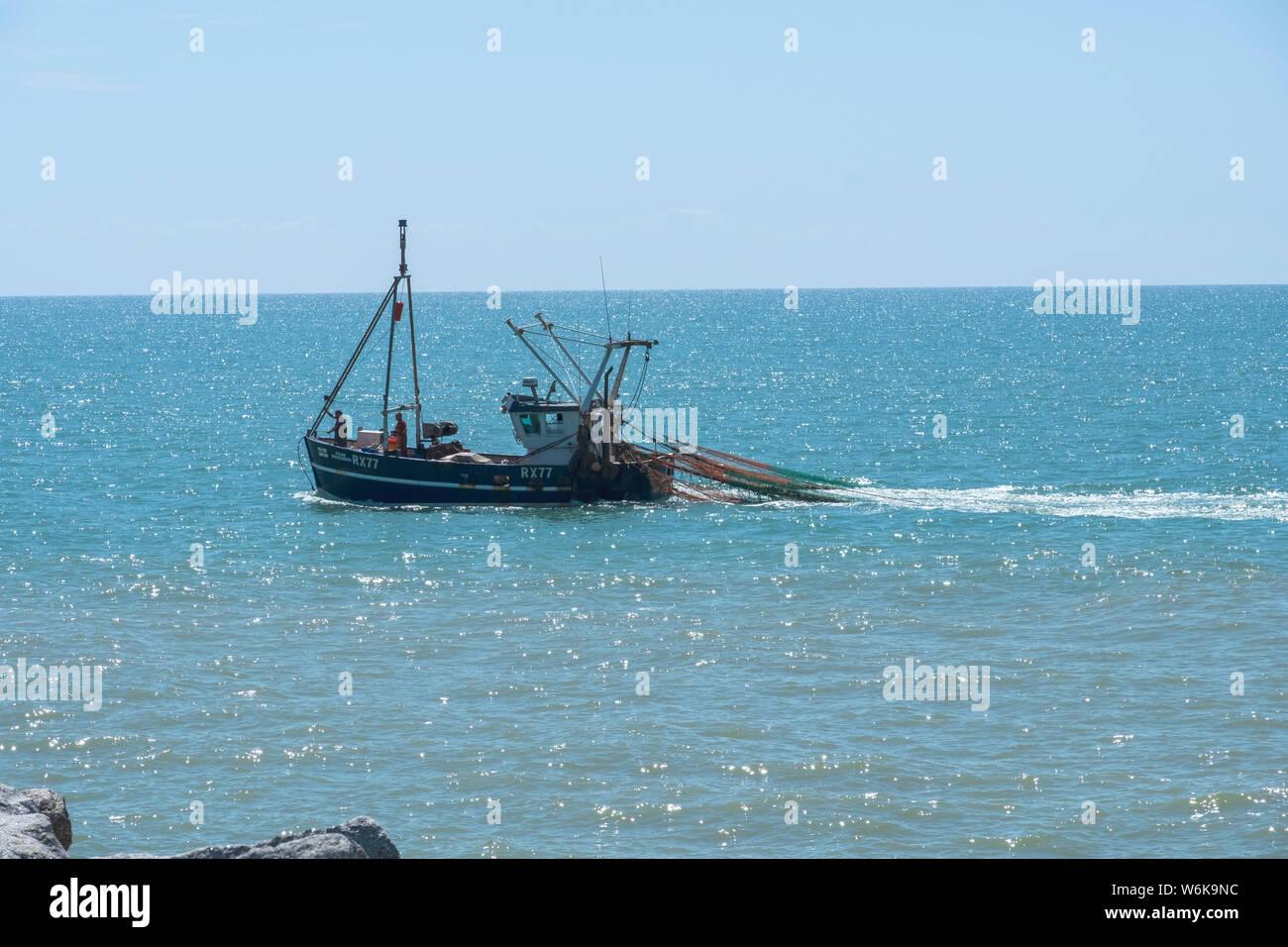 La pesca de arrastre de Hastings regresan a Puerto con las redes de arrastre fuera cerca de la orilla, East Sussex, Reino Unido Foto de stock