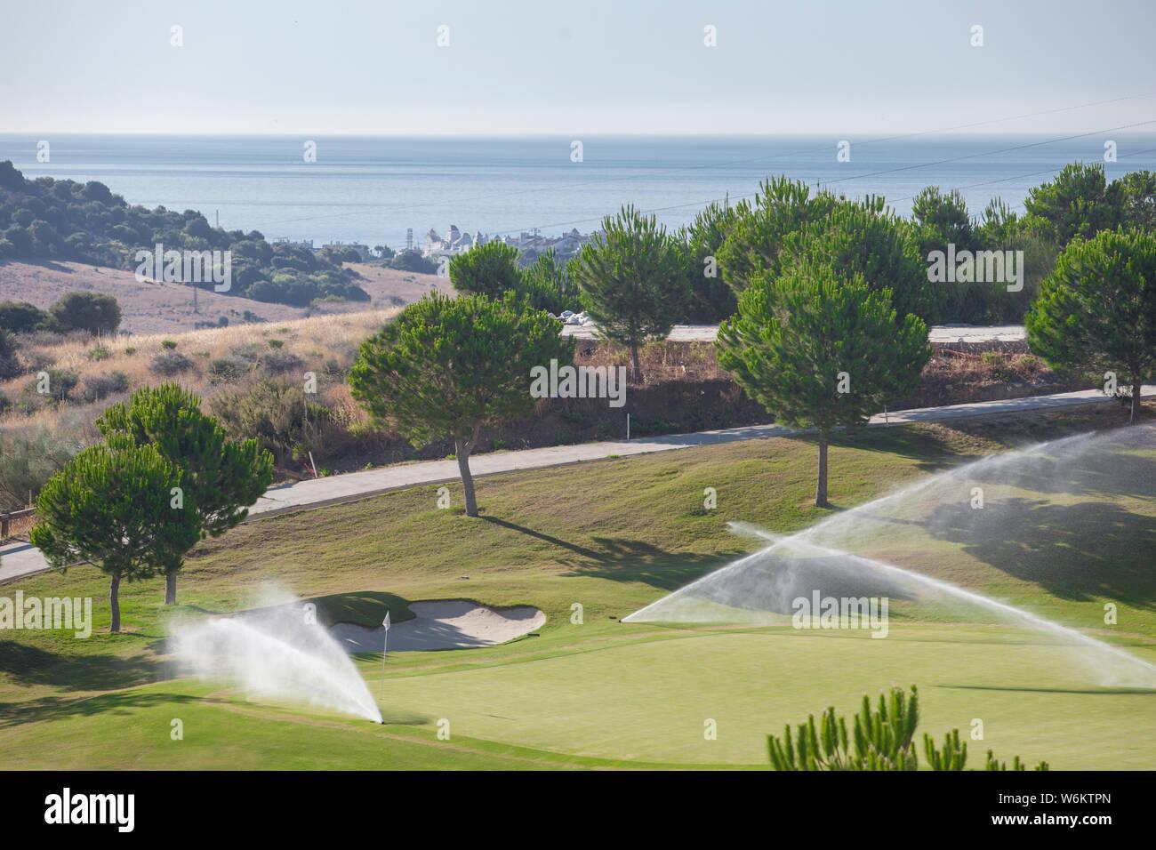 Sistema de riego Aspersores trabajando en el verde del campo de golf. La Costa del Sol, Málaga, España Foto de stock