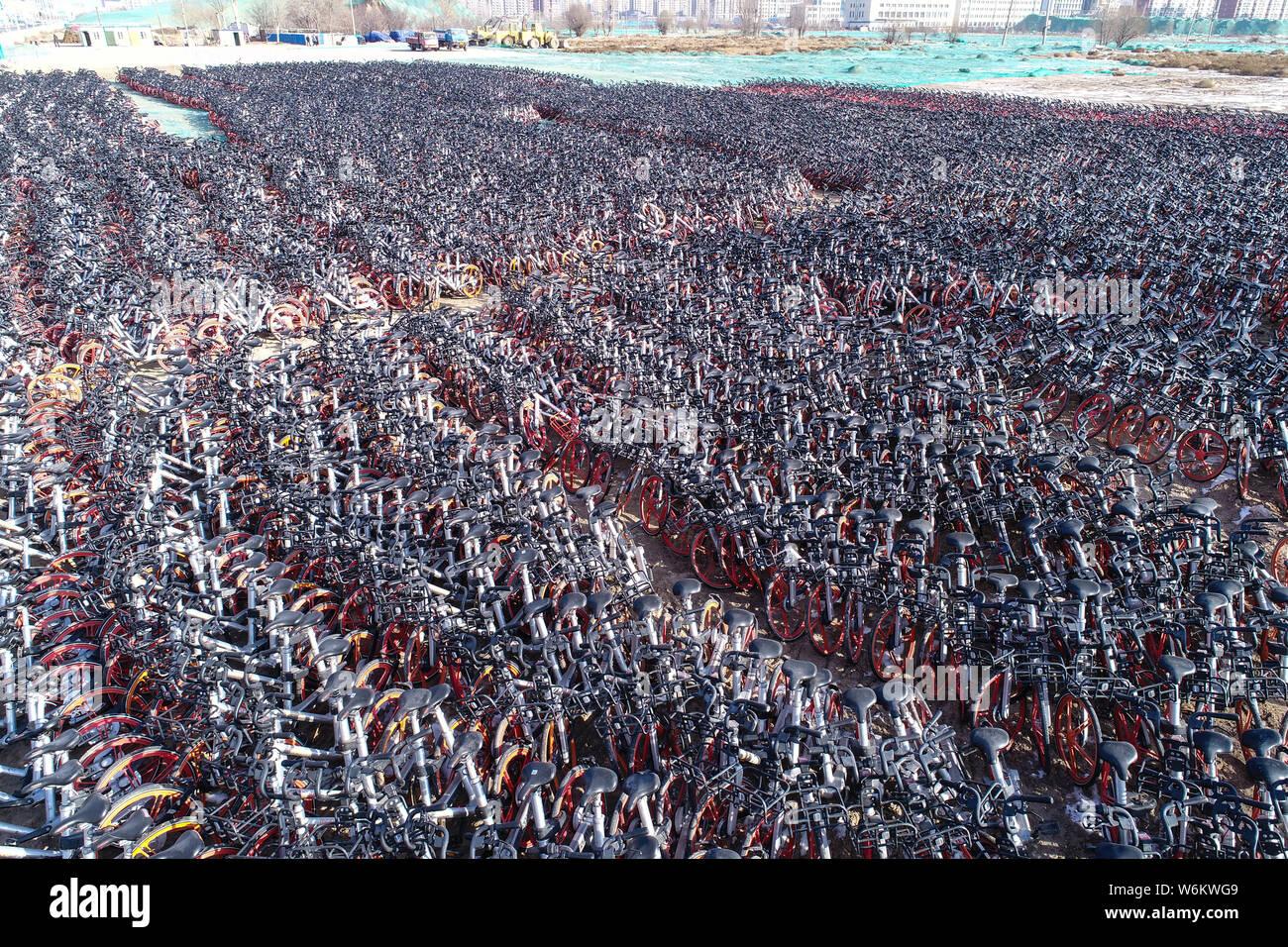 Miles de bicicletas de servicio de bicicletas compartidas Mobike están alineadas en un espacio abierto en la ciudad de Yinchuan, al noroeste de China, la región autónoma de Ningxia Hui Foto de stock