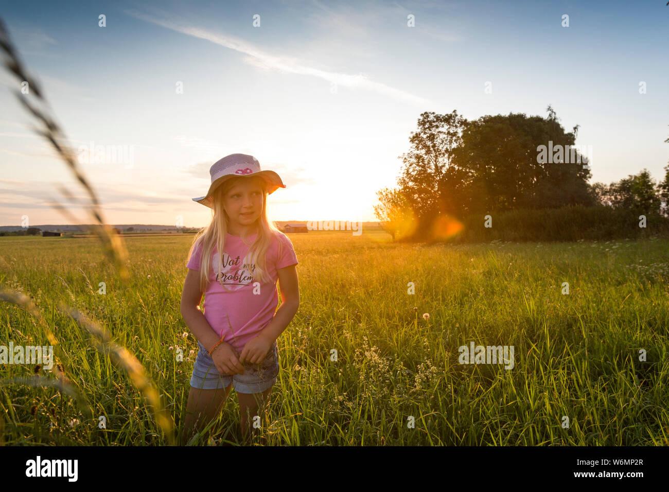 Niña feliz disfrutando de la puesta de sol en el campo Foto de stock