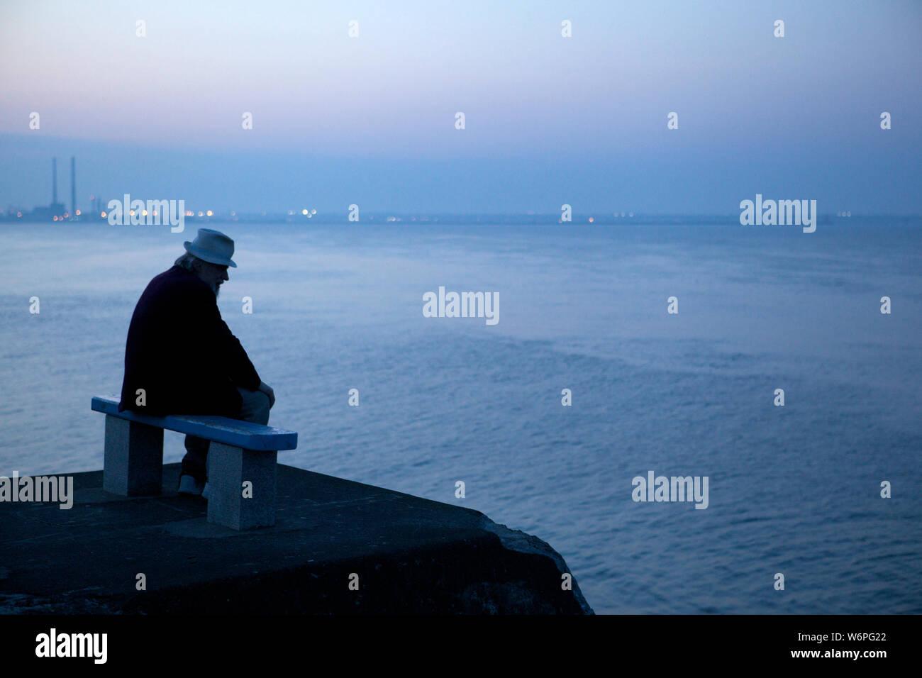 Anciano sentado en un banco en el mar Foto de stock