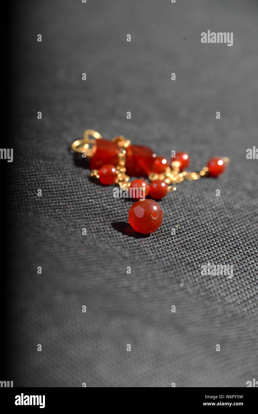 Joyas de oro rojo en el cuadro de cierre muy bonito con fondo gris brillante brazalete o collar pendientes cristal naranja Foto de stock