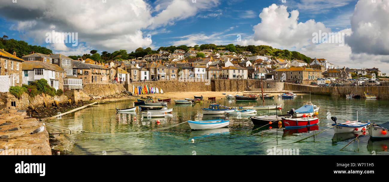 Reino Unido, Inglaterra, Cornwall, Mousehole, barcos amarrados en el puerto en marea baja por debajo de South Cliff, panorámicas Foto de stock