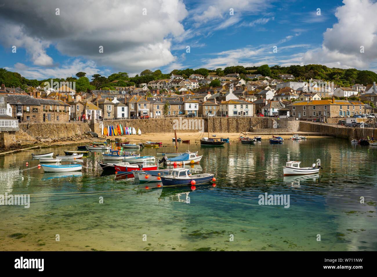 Reino Unido, Inglaterra, Cornwall, Mousehole, barcos amarrados en el puerto en marea baja por debajo de South Cliff Foto de stock