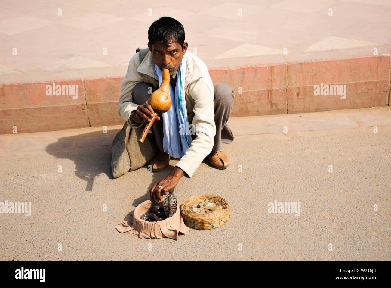 Domador de serpientes indio jugar y encantadores de serpientes cobra mostrar en las calles para el pueblo indio y los viajeros extranjeros en la puerta de la India en Nueva Delhi, el 17 de marzo de 2019 Foto de stock