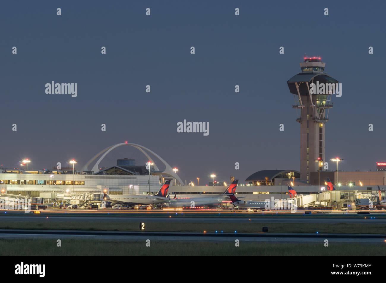 Imagen de la construcción del tema y la torre de control y Delta Air Lines chorros en la puerta en el Aeropuerto Internacional de Los Angeles, LAX, al anochecer. Foto de stock